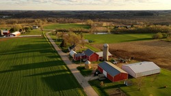 American midwestern countryside in springtime. Aerial view of farms with red barns in spring, rural road, agricultural fields