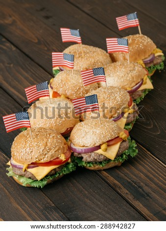 American mini beef burgers with cheese and USA flags, on the old wooden table. Selective focus and small depth of field.