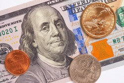 American money: a note of 100 US dollars, coin of 1 dollar, a quarter (25 cents) and a penny (1 cent) lie on a white paper background. Not isolated. FED, refinancing rate. View from above. Macro