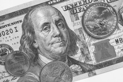 American money: a note of 100 US dollars, coin of 1 dollar, a quarter (25 cents) and a penny (1 cent). Black and white background or wallpaper on a commercial, financial or banking theme. Macro