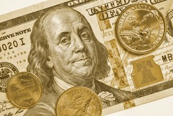 American money: a note of 100 US dollars, coin of 1 dollar, a quarter (25 cents) and a penny (1 cent). Green or yellow tinted background or wallpaper on a commercial, financial or banking theme. Macro