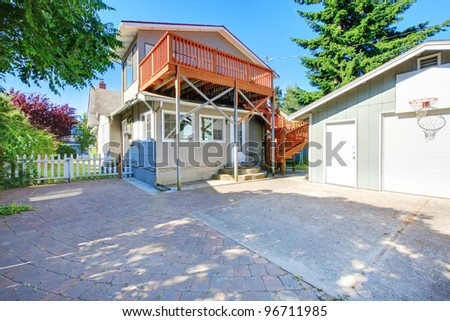 American old house with a new large deck. View from the back yard with garage.
