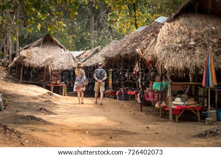 Shutterstock American or european couple of tourists visiting a long-necked Karen village in a tribe near Chiang Mai in Northern Thailand. A place to see Giraffes women. Chiang Mai - Thailand.