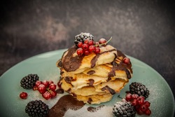 American pancakes topped with chocolate.  Homemade dessert with fruit and chocolate syrup
