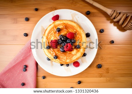 American pancakes with blueberries and raspberry, over wooden surface - top view