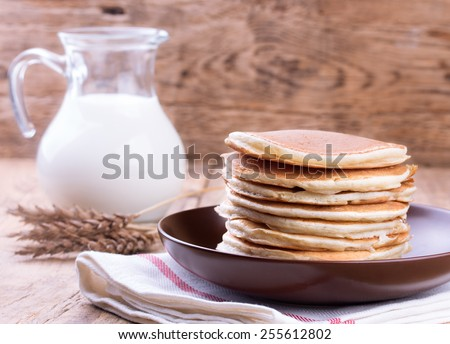 American pancakes with jug of milk on wooden background