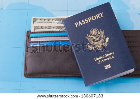 American passport and wallet with dollars cash and credit cards on map background for business travel concept.