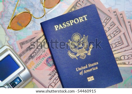 American passport over US money with sunglasses and digital camera on a travel map for a getaway