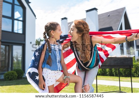 American patriots. Happy nice mother and daughter laughing while celebrating a holiday together #1156587445