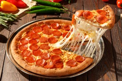 American pizza with pepperoni, mozzarella and tomato sauce. Pizza on a wooden table, morning, dawn.