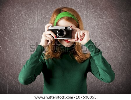 American redhead girl with camera. Photo in 60s style.
