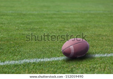 American rugby ball on the grass in the stadium