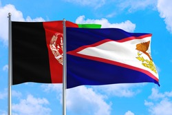American Samoa and Afghanistan national flag waving in the wind on a deep blue sky together. High quality fabric. International relations concept.