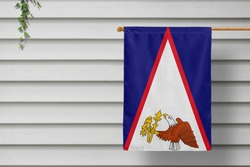 American Samoa national small flag hangs from a picket fence along the wooden wall in a rural town. Independence day concept.