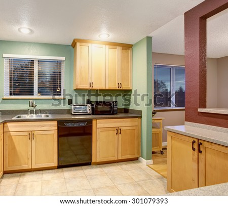 American small house or apartment type typical kitchen for 2014. Tile floor, birch tree light wood cabinets, black color applicances  #301079393