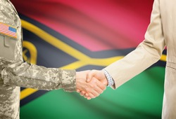 American soldier in uniform and civil man in suit shaking hands with adequate national flag on background - Vanuatu