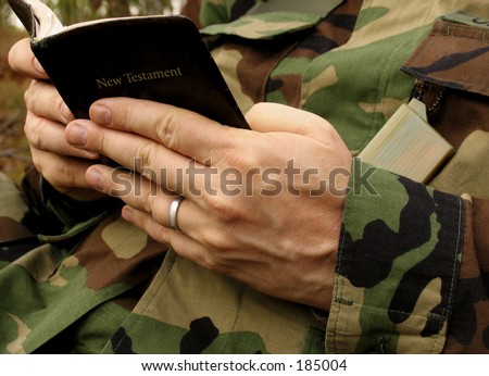 american soldier's hands in uniform reading Bible