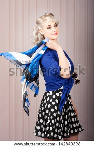American style pin-up girl strolling with classic hairstyle and makeup on vintage stripe background