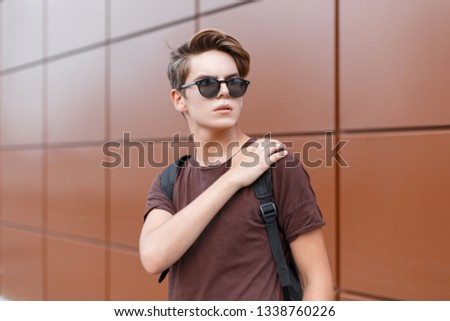 American stylish hipster young man in a brown stylish t-shirt in dark sunglasses with a trendy hairstyle with a trendy black backpack stands near the wall. Handsome modern guy. Summer style. #1338760226