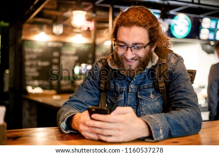 American traveler in a denim jacket sitting at the table of the tavern