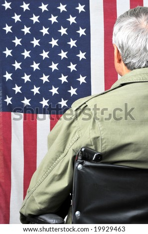 American veteran in wheelchair and fatigues facing flag - stock photo