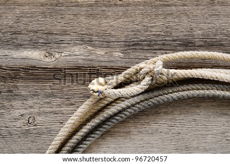 American West authentic rodeo cowboy lariat lasso hondo or honda noose with end loop rawhide speed burner on old and weathered aged barn wood