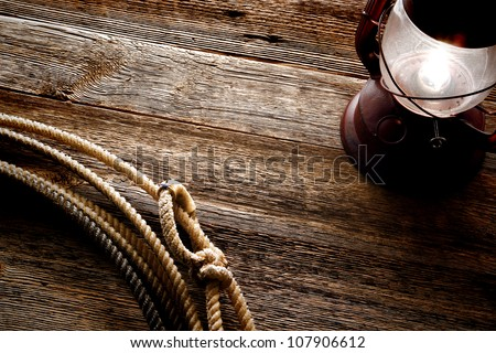 American West authentic rodeo cowboy lariat lasso noose with rawhide speed burner on weathered and aged barn wood background lit by an old vintage kerosene lantern lamp