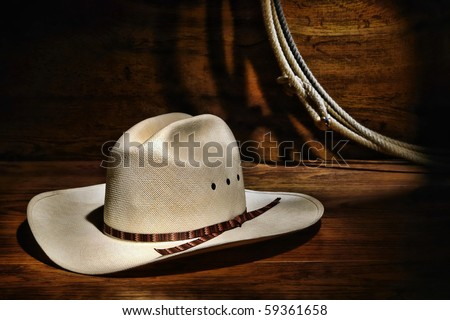 American West rodeo authentic cowboy white straw hat and lasso rope in a ranching wood barn