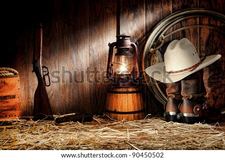 American West rodeo cowboy authentic working gear with straw hat on roper leather boots and old Western rifle gun in vintage ranch wood barn with ranching tools lit by old nostalgic kerosene oil lamp