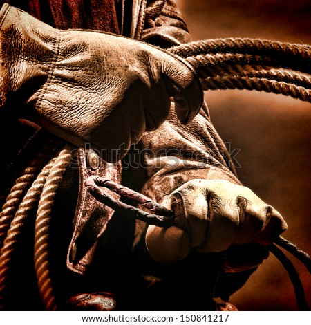 American West Rodeo Cowboy Hands Wearing Rancher Gloves Holding A Roping Lasso Lariat Rope While Riding On An Old Western Saddle