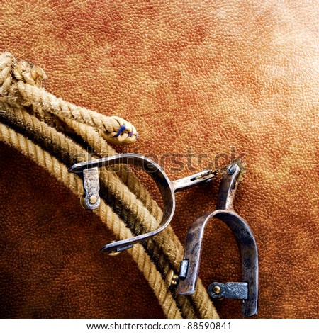 American West rodeo cowboy lariat lasso with cutting and roping spurs on old brown leather grunge background