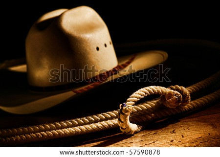American West rodeo cowboy lasso rope and white straw hat in dramatic light with dark shadows
