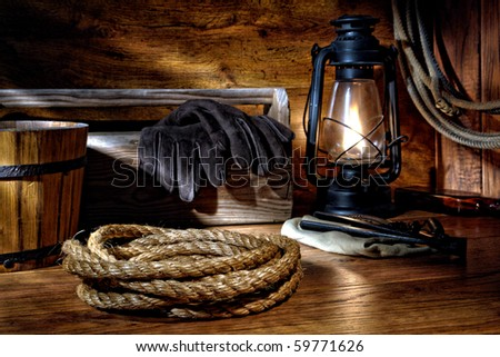 American West rodeo cowboy ranching rope with old burning kerosene oil lamp and traditional rancher tools over wood in a vintage ranch barn