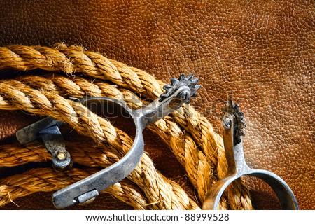 American West rodeo cowboy ranching rope with western riding spurs on old brown leather grunge background