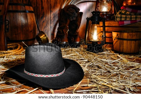 American West rodeo cowboy traditional black felt hat on straw covered wood floor in vintage ranch barn with antique ranching supplies and rancher tools lit by old nostalgic kerosene lantern oil lamps