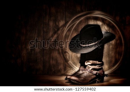 American West rodeo cowboy traditional black felt hat resting atop worn leather working rancher roper boots and lasso lariat in a vintage ranch wood barn lit in moonlight diffused glow