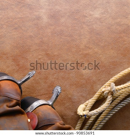 American West rodeo cowboy traditional leather boots with riding spurs and authentic Western lasso lariat with hondo or honda loop on brown leather texture background