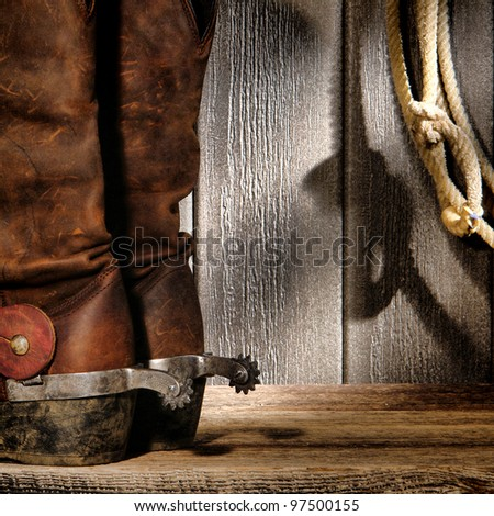 American West rodeo cowboy traditional leather boots with roping riding spurs and authentic Western lasso lariat on weathered barn wood background