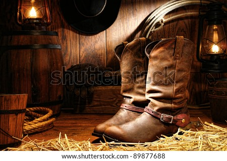 American West rodeo cowboy traditional leather working rancher roper boots with authentic Western riding spurs in a vintage ranch barn with ranching tools lit by old nostalgic kerosene oil lamps