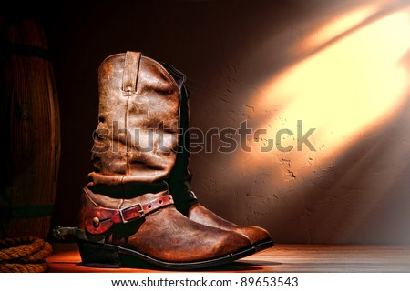 American West rodeo cowboy traditional leather working roper boots with authentic Western riding spurs in a vintage ranch barn