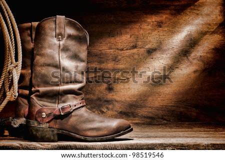 American West rodeo cowboy traditional leather working roper boots with authentic Western riding spurs and roping lasso lariat on a vintage ranch barn old weathered wood floor