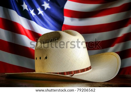 American West rodeo cowboy traditional white straw hat over waving old and antique historic US flag at a patriotic Western event
