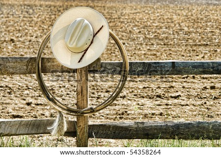 American West rodeo cowboy white straw hat and roping lasso hanging on an old wood fence post on an agriculture farm field at a Western ranch