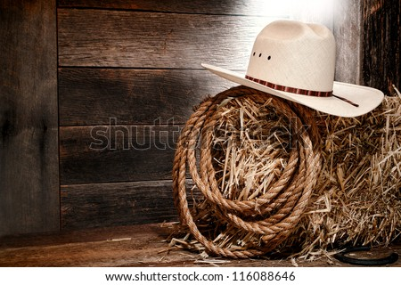 American West rodeo cowboy white straw hat with traditional western ranching rope on a bale of hay in an old wood ranch barn lit by diffused light