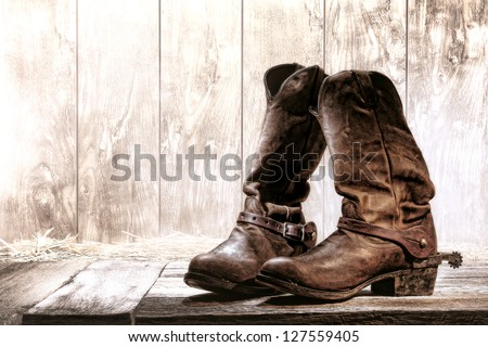 American West rodeo pair of traditional leather roper style western riding slouch cowboy boots with authentic ranching spurs on wood deck in front of an old ranch wood barn