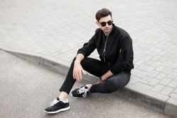 American young man model in a fashionable jacket in black jeans in sneakers in dark sunglasses is sitting on the tile on a street in the summer day. Modern guy hipster is resting in the city. Menswear