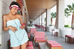 Americana black teenager girl standing at bar on a summer bright day, using a smartphone and headphones to enjoy listening to music, smiling. Fun technology and retro adolescent lifestyle, outdoors.