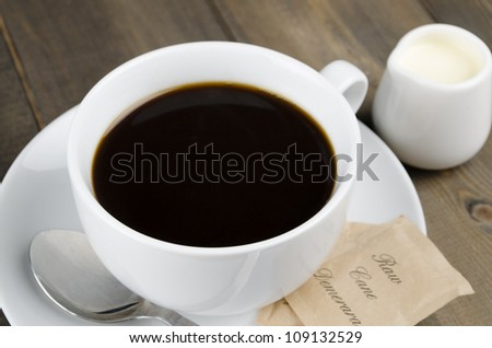 Americano black coffee in a white cup with raw demerara sugar sachets and a jug of milk. Close up.