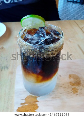Americano iced coffee, Americano is cold in a clear glass with lime and sugar granules.