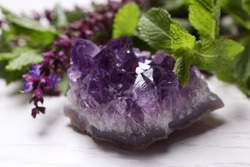 Amethyst gemstone and healing herbs on white wooden table, closeup